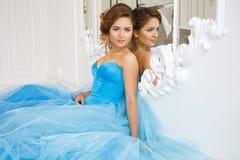 华美的蓝色礼服灰姑娘样式的美丽的新娘在镜子附近 库存图片