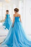 华美的蓝色礼服灰姑娘样式的美丽的新娘在镜子附近 免版税图库摄影