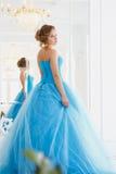 华美的蓝色礼服灰姑娘样式的美丽的新娘在镜子附近 图库摄影