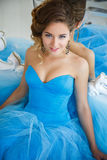 华美的蓝色礼服灰姑娘样式的美丽的新娘在镜子附近 免版税库存图片