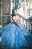 华美的蓝色长的礼服的美丽的少妇象有完善的构成和发型的灰姑娘 库存图片