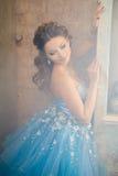 华美的蓝色长的礼服的美丽的少妇象有完善的构成和发型的灰姑娘 免版税库存图片
