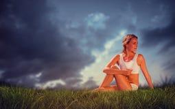 华美的适合金发碧眼的女人的综合图象供以座位的瑜伽姿势的 库存照片