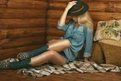 华美的长腿的女孩佩带的牛仔裤短裤、衬衣、绒面革靴子有花卉刺绣的和斯泰森呢帽画象  库存照片