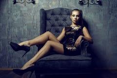 年轻华美的长腿的模型画象与穿短的衣服饰物之小金属片金黄礼服的马尾辫和艺术性的构成的 免版税库存照片