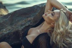 华美的魅力晒黑了有佩带黑泳装和夏天长袍的闭合的眼睛的白肤金发的妇女放松和沐浴在阳光下 免版税库存照片