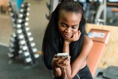 华美的黑人夫人画象有发短信在她的在健身房的智能手机的豪华长的头发的 图库摄影