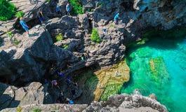 华美的令人惊讶的自然岩石、峭壁视图和平静的天蓝色的清楚的水与 图库摄影