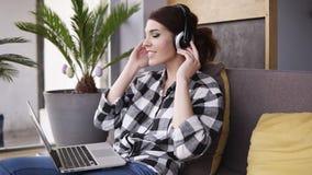 华美,少妇放松坐长沙发,投入耳机并且打开在膝上型计算机的音乐 微笑和移动向 影视素材