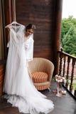 华美,愉快的在佩带前的微笑新娘尝试的婚礼礼服 早晨准备 投入在木的礼服的妇女 库存照片