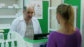 协助一名女性顾客的资深药剂师在队列的头在药房 股票视频