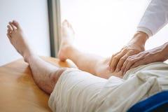 协助一名男性患者的医生生理治疗师,当给行使按摩患者的腿的治疗在一间理疗的屋子,时 免版税库存图片