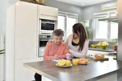 协助一名年长妇女的家庭护工 库存照片