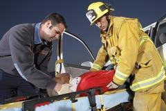 协助人的消防队员和医务人员在失事地点 免版税图库摄影