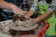 协助他的做的男性陶瓷工罐女儿 免版税库存照片