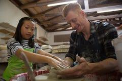 协助他的做的男性陶瓷工罐女儿 免版税库存图片
