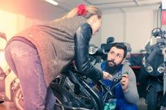 协助修理的年轻男性工作者motorcy女性顾客 库存照片