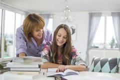 协助做的微笑的母亲家庭作业女儿在桌上 免版税库存图片