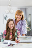 协助做的愉快的母亲画象家庭作业女儿在桌上 库存照片