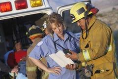 协助受伤的人的消防队员和医务人员 免版税库存照片