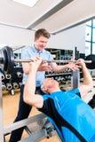 协助在健身房的教练员老人举的杠铃 库存图片