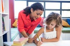 协助在笔记本的老师女孩文字在图书馆里 免版税库存图片