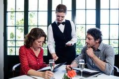 协助夫妇的女服务员,当选择菜单时 免版税库存图片