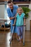 协助女孩患者的生理治疗师走与拐杖 库存照片