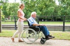 协助她的轮椅的微笑的少妇残疾父亲 库存照片