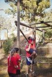 协助孩子的教练员攀登在新兵训练所的一条绳索 库存图片