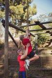 协助孩子的教练员攀登在新兵训练所的一条绳索 图库摄影