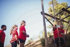 协助孩子的教练员攀登在新兵训练所的一条绳索 免版税库存照片