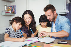 协助孩子的父母做家庭作业 库存照片