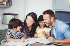 协助家庭作业的快乐的父母孩子 免版税库存照片