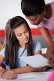 协助少年女小学生的老师在期间 免版税库存照片