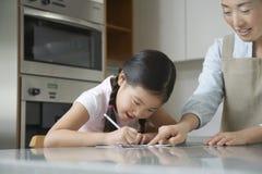 协助有家庭作业的母亲女孩 库存图片