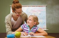 协助有家庭作业的老师女孩在教室 免版税图库摄影