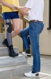 协助有腿的治疗师被截肢者在台阶 免版税库存照片