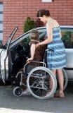 协助残疾妇女的女孩进入汽车 免版税库存照片