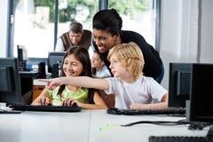 协助男孩的老师指向在计算机上在实验室 免版税库存图片