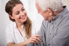 协助老人的微笑的护士 免版税库存图片