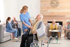 协助老年人的护士 库存照片