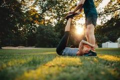 协助腿的个人教练员妇女舒展锻炼 库存图片