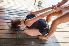 协助舒展的健身辅导员锻炼少妇 图库摄影