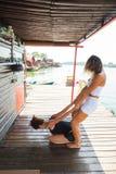 协助舒展的健身辅导员锻炼少妇 免版税库存照片