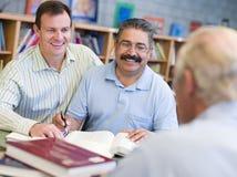 协助解决图书馆成熟学员家庭教师 免版税库存照片