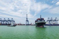 协助解决容器货船的拖轮 免版税图库摄影