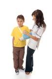 协助解决男孩被伤害的护士 免版税图库摄影