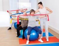 协助资深人民的教练员在健身房 免版税库存照片