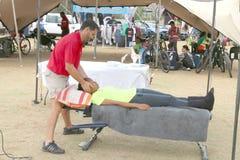 协助骑自行车者的按摩医生在终点线在Mathaithai 免版税库存照片